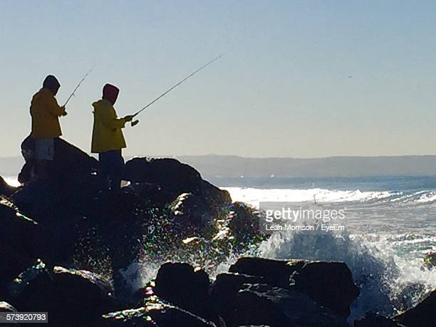 People Fishing On Rock Shore Against Clear Sky
