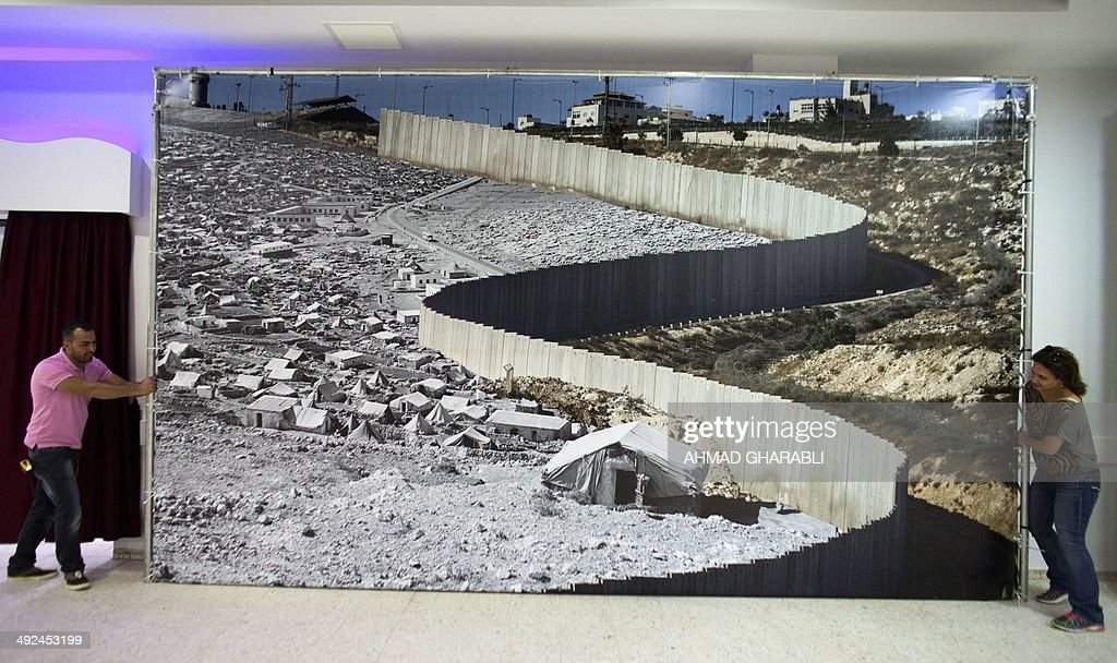 People fix a photo montage of old and recent images of Palestinian refugees' camps separated by Israel's separation barrier at they set up an exhibition at a community center in the Palestinian refugee camp of Dheisheh near the West Bank city of Bethlehem May 20, 2014 ahead of Pope Francis' visit to the camp. The pope's visit is scheduled to begin in Jordan on May 24, and he is then due to spend two days in the Holy Land from May 25.