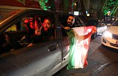 People flash the 'V for Victory' sign and hold an Iranian flag out of a car window as they celebrate on Valiasr street in northern Tehran on April 2...