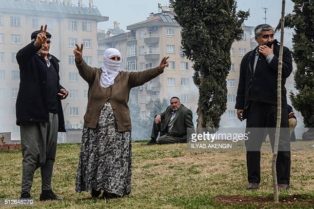 People flash victory sign as Turkish police fire tear gas in Diyarbakir on February 27 2016 during a demonstration against governmentimposed curfews...