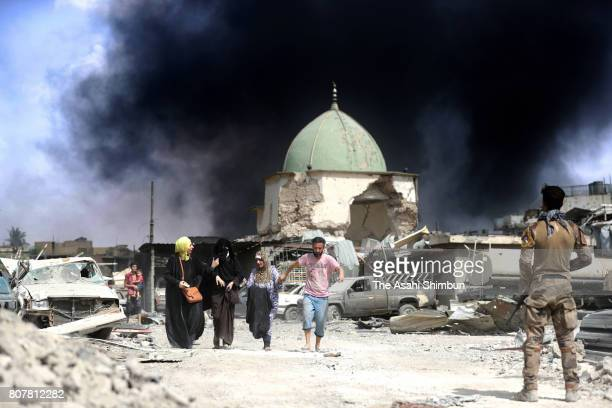 People fleed from alNuri Mosque as the Iraqi force battle to retake the Old City from the Islamic States on July 2 2017 in Mosul Iraq