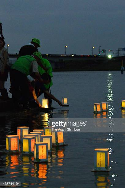 People float candlelit paper lanterns on Chikugogawa River to commemorate ancestors' souls during the Toro Nagashi on August 15 2014 in Kurume...