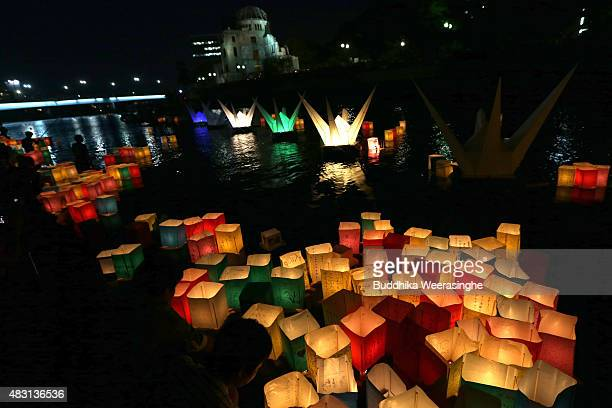 People float peace messages written on paper lanterns along the river during the 70th anniversary activities commemorating the atomic bombing of...
