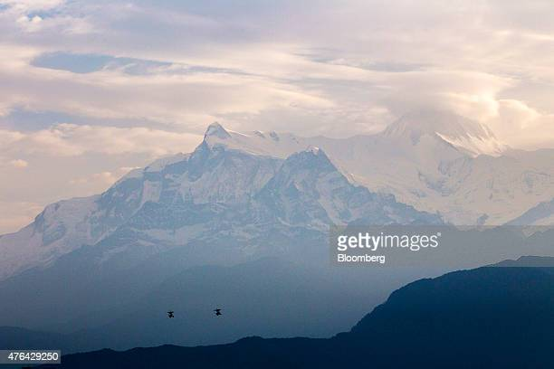 People fly in paramotors as the Annapurna mountain range stands in the background in Pokhara Nepal on Tuesday June 2 2015 Nepal's gross domestic...