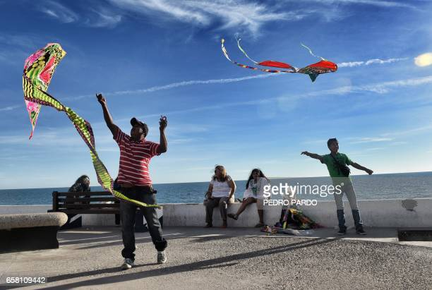 People fly kites at the Malecon in Puerto Penasco Sonora state Mexico on March 26 2017 / AFP PHOTO / PEDRO PARDO