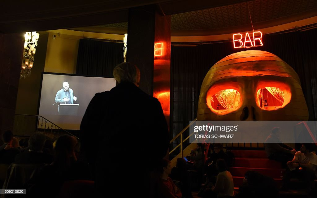 People follow the speech of Greek former Finance Minister Yanis Varoufakis during an event to mark the official launch of the Democracy in Europe Movement (DiEM) in Berlin on February 9, 2016. / AFP / TOBIAS SCHWARZ
