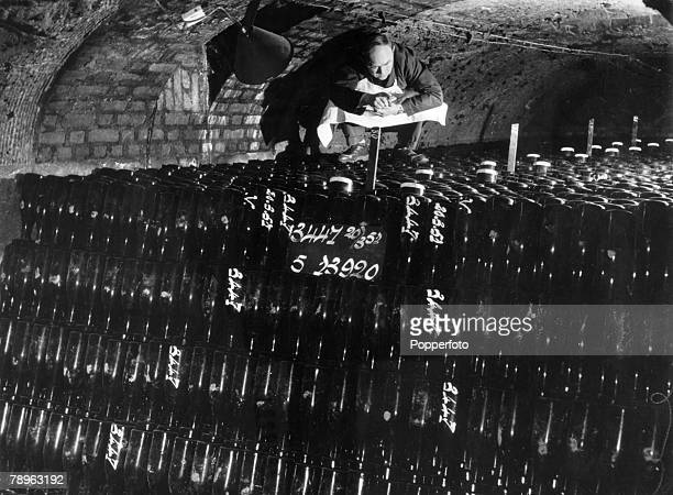 circa 1951 The grape harvest the image shows a French cellar in the Rheims Epernay area of France where a worker is doing his weekly check on the...