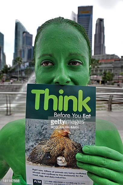 People for the Ethical Treatment of Animals campaigner Ashley Fruno covered from head to toe in brightgreen body paint holds a pamphlet that reads...