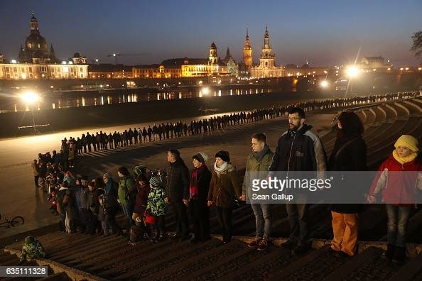 People form a human chain across from the rebuilt historic city center to both commemorate the 72nd anniversary of the Dresden firebombing and to...