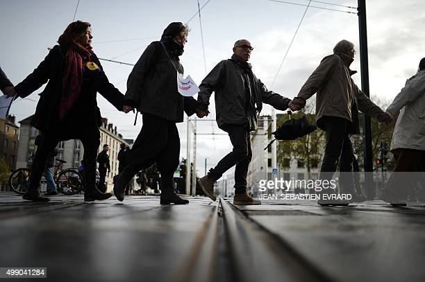 People form a human chain in Nantes western France on November 28 2015 during a protest called by various parties associations and trade unions...