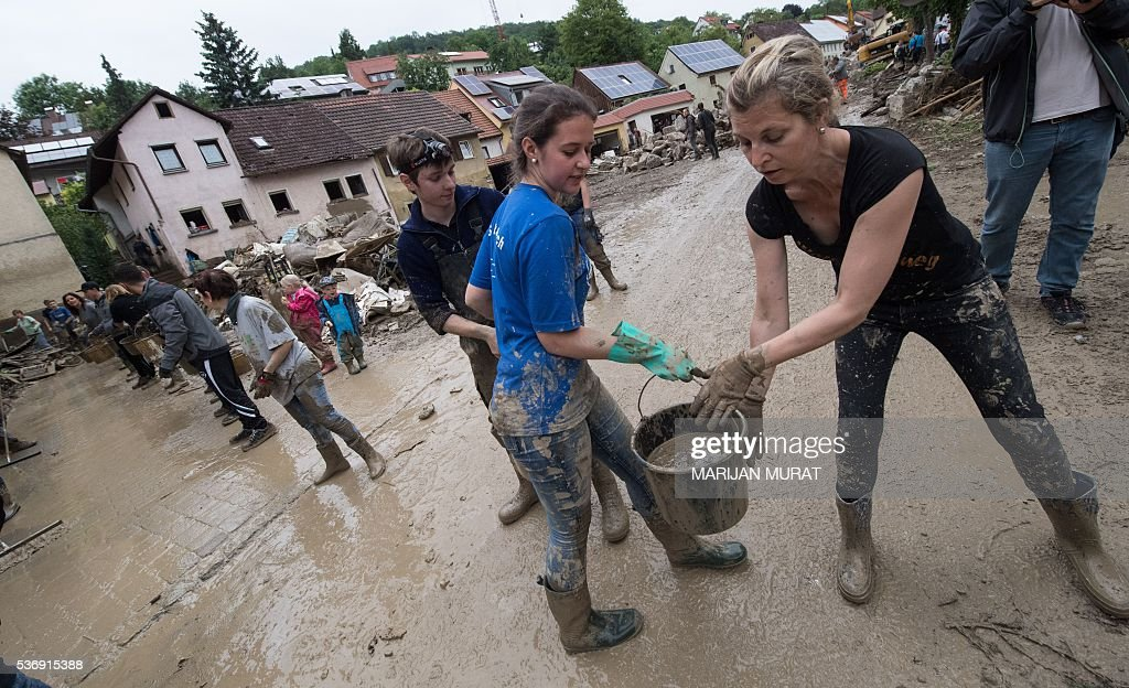 People form a human chain to remove water in buckets from flooded houses in Braunsbach southern Germany on June 1 2016 Incessant rain in regions of...