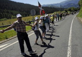 People form part of a human chain in Kanpazar mountain next to the Basque village of Mondragon northern Spain on June 8 2014 during a protest action...