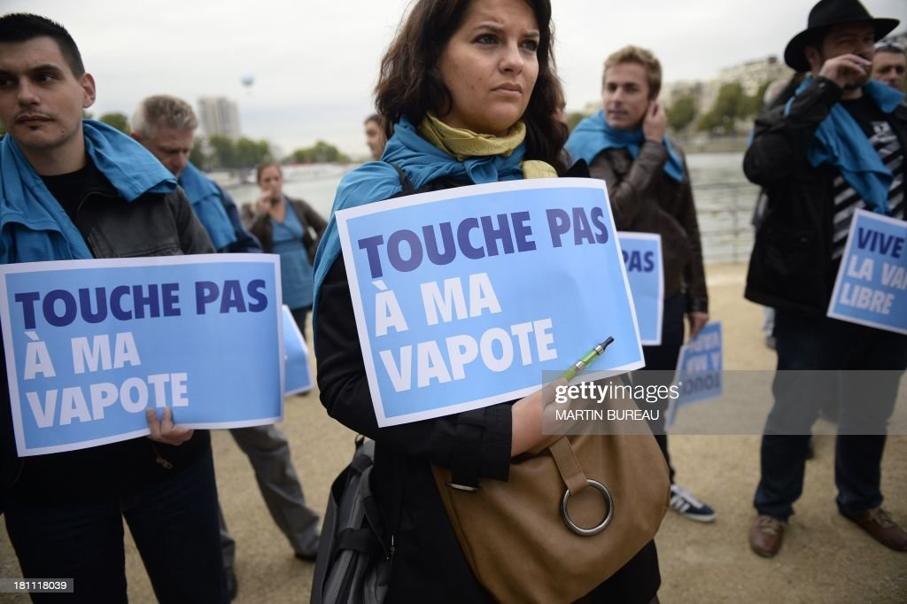 People from a European movement defending the use of electronic cigarettes demonstrate while holding placards reading 'Don't touch my vapour' (in relation to e-cigarettes) on September 19, 2013 in Paris. AFP PHOTO / MARTIN BUREAU