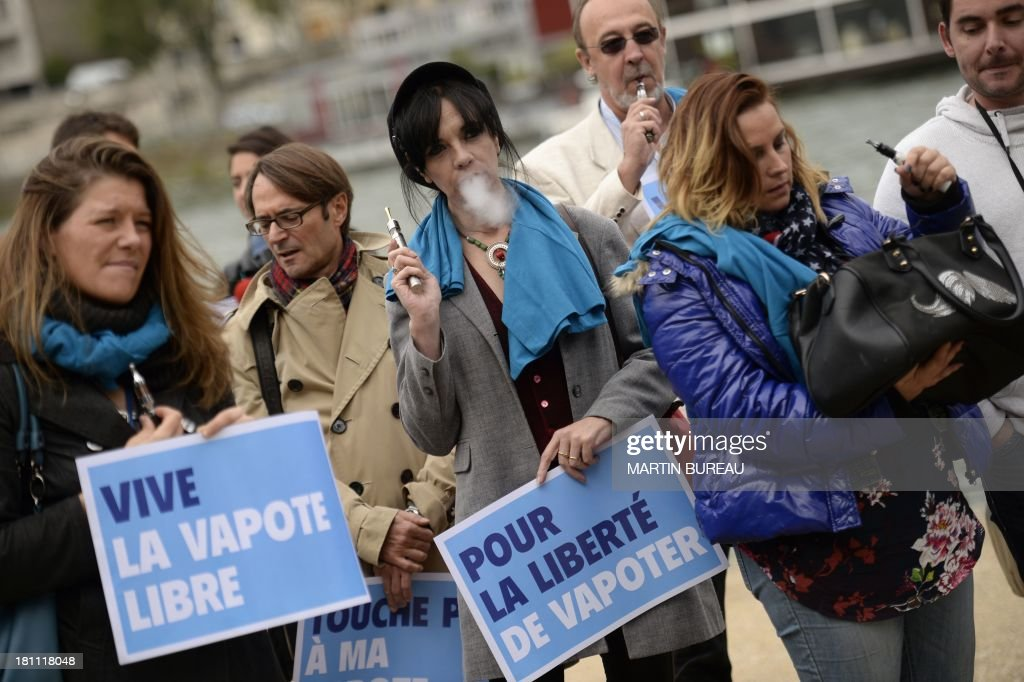 People from a European movement defending the use of electronic cigarettes demonstrate while holding placards reading 'Long live the free vapour' (L) and ' For the liberty of vapouring' (in relation to e-cigarettes) on September 19, 2013 in Paris.