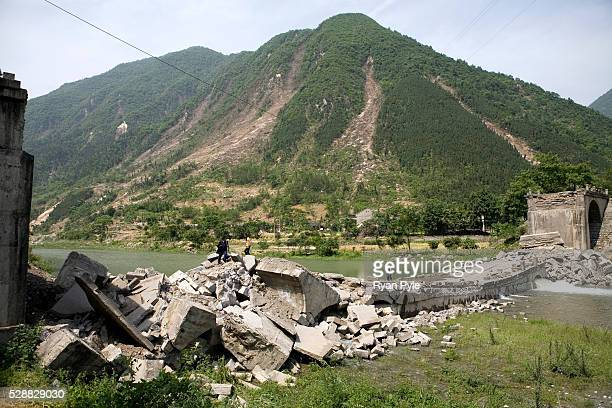 People from a nearby village cross a collapsed bridge in Beichuan county Sichuan China A 79 magnitude earthquake that struck China's Sichuan province...
