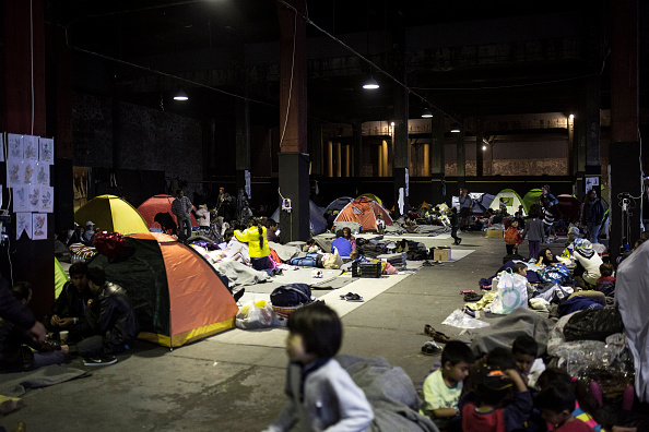 People from Afghanistan go about with their daily life in a migrant and refugee makeshift camp inside a building at Piraeus harbour in Athens, on March 6, 2016. At least 25 migrants including child...