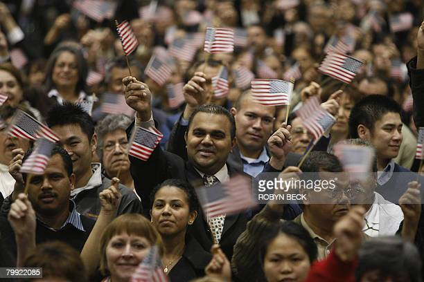 People from approximately 100 different countries wave flags at a citizenship oathtaking ceremony where they became naturalized US citizens in Los...