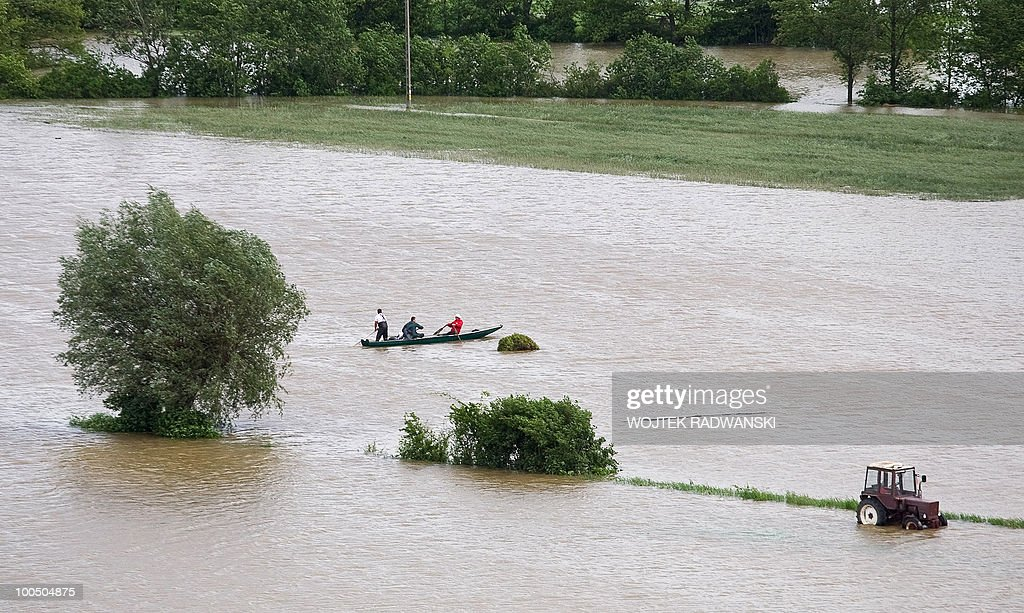People from flooded houses in Swiniary village row a boat in the flooded area of the village in central Poland, at Wisla river, on May 25, 2010. Floods caused by torrential rains last week have swollen major Polish rivers to their highest levels in more than a century and have claimed 15 lives.