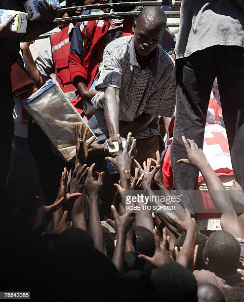 People from Kibera raise their arms as they crowd a relief food truck from the Kenyan Red Cross at the Salvation Army church grounds in the Kibera...