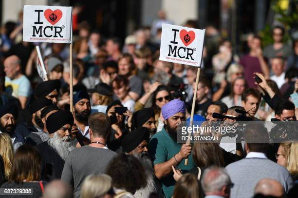 TOPSHOT People from Manchester Sikh Community carry 'I love MCR' banners as they arrive to attend a vigil in Albert Square in Manchester northwest...