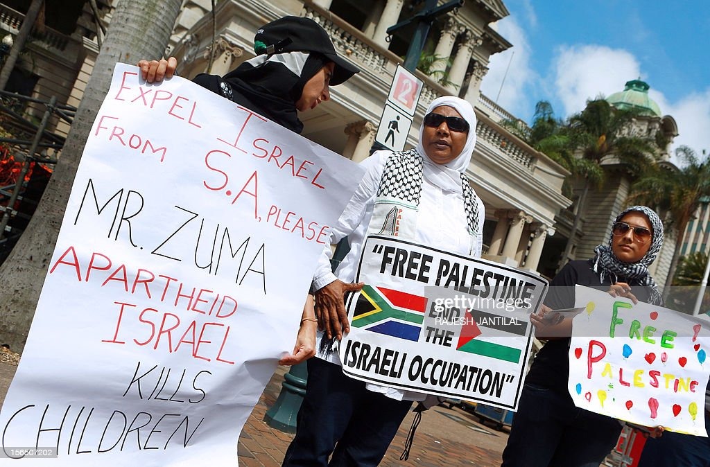 People from the Coalition for a Free Palestine (CFP) hold sign as they gather outside the Durban City hall on November 16, 2012 to protest against the Israeli bonbardment of Gaza.The demonstrators called on South African President Jacob Zuma to recall the South African ambassador in Tel Aviv and to expel the Israeli ambassador. Some of them were singing ' Down with Apartheid Israel Down' and 'Stop the killings of innocent children of Gaza'.