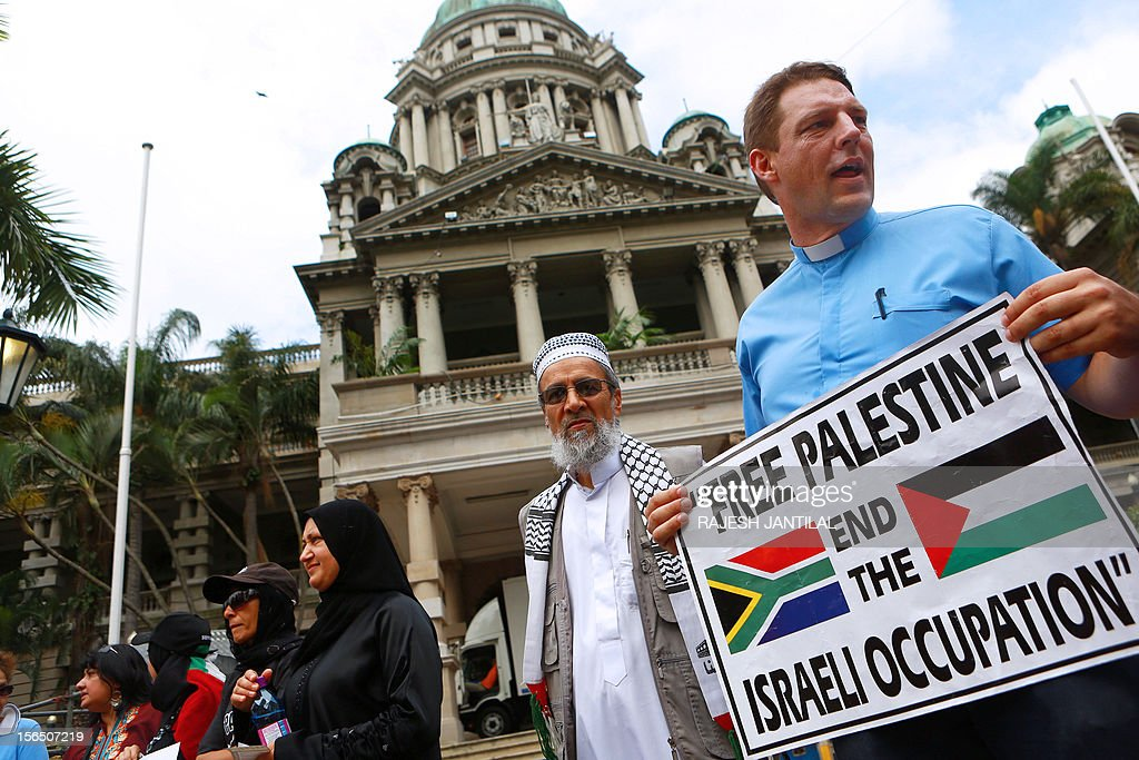 People from the Coalition for a Free Palestine (CFP) hold signs as they gather outside the Durban City hall on November 16, 2012 to protest against the Israeli bonbardment of Gaza.The demonstrators called on South African President Jacob Zuma to recall the South African ambassador in Tel Aviv and to expel the Israeli ambassador. Some of them were singing ' Down with Apartheid Israel Down' and 'Stop the killings of innocent children of Gaza'.