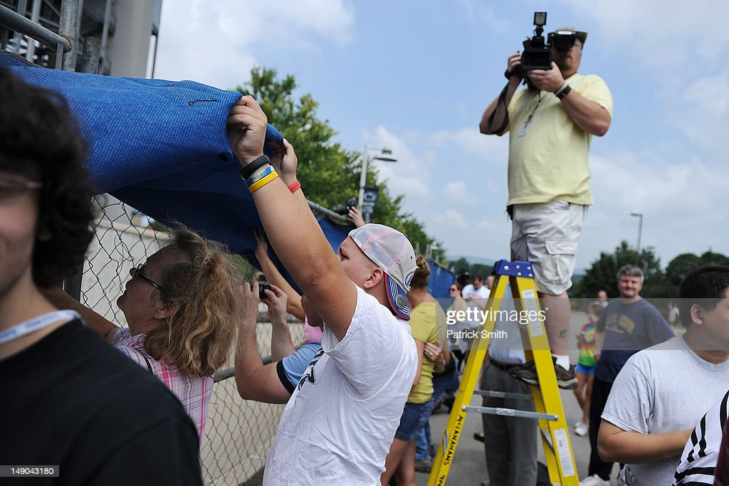 People from the community take pictures at the site in which the statue of former Penn State University football coach Joe Paterno stood sits empty after it was removed by workers outside Beaver Stadium on July 22, 2012 in State College, Pennsylvania. Penn State's president Rodney Erickson made the decision Sunday to remove the statue in the wake of the child sex scandal of former assistant football coach Jerry Sandusky. It's believed that Paterno had detailed knowledge of Jerry Sandusky sexually abusing children before and after Sandusky retired from coaching at Penn State.