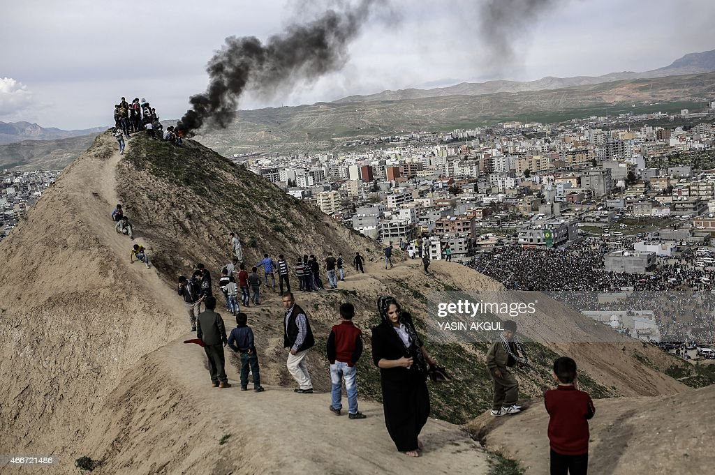 People from the Kurdish community gather on a hillside as they light a fire as part of celebrations surrounding Newroz which marks the arrival of...