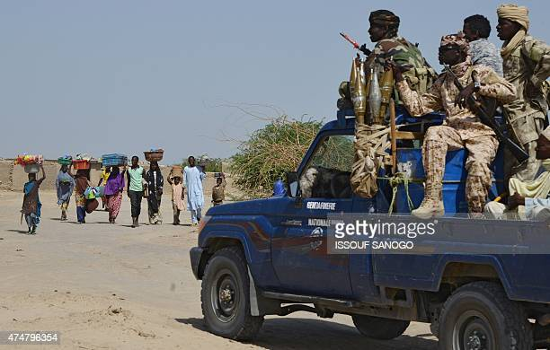 People from the Nigerian town of Malam Fatori an its area close to the borders with Niger and Chad pass by a car with Chadian Gendarmes as they flee...