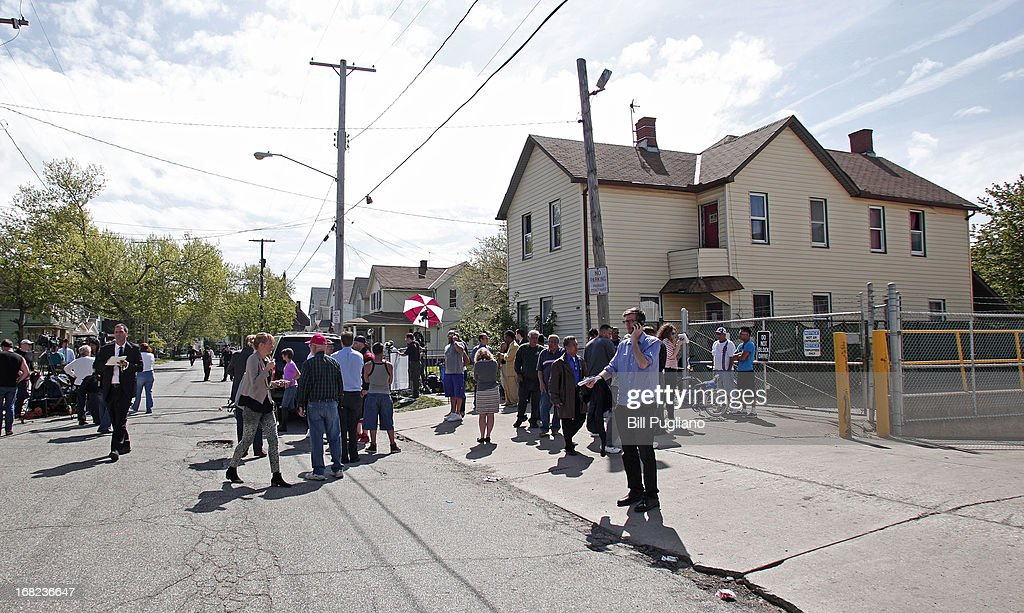 People gather along Seymour Avenue near the house where three women, who disappeared as teens about a decade ago, were found alive May 7, 2013 in Cleveland, Ohio. Amanda Berry, who went missing in 2003, Gina DeJesus, who went missing in 2004, and Michelle Knight, who went missing in 2002, managed to escape their captors on May 6, 2013. Three suspects, all brothers, were taken into custody.