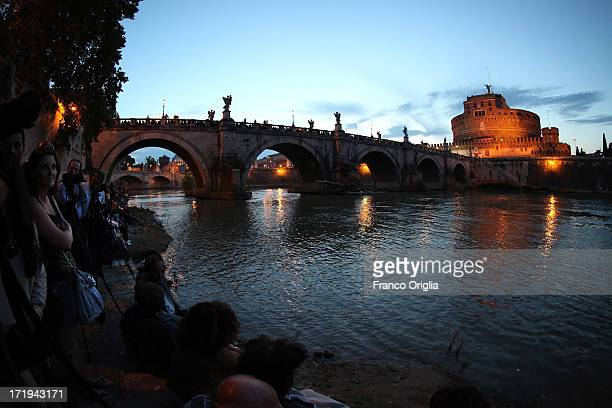 People gather along the Tiber to wait for the traditional 'La Girandola' fireworks over Castel Sant'Angelo on June 29 2013 in Rome Italy The...