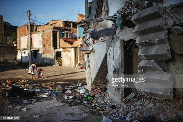 People gather amidst the rubble of destroyed homes in the MetroMangueira community or 'favela' located approximately 750 meters from Maracana stadium...