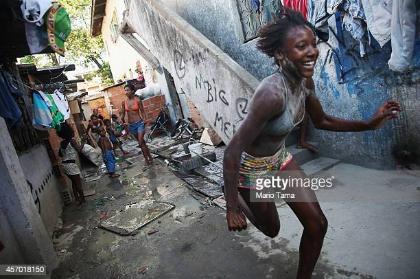 People gather and play in a delapidated section of the occupied Complexo da Mare one of the largest favela complexes in Rio on October 10 2014 in Rio...