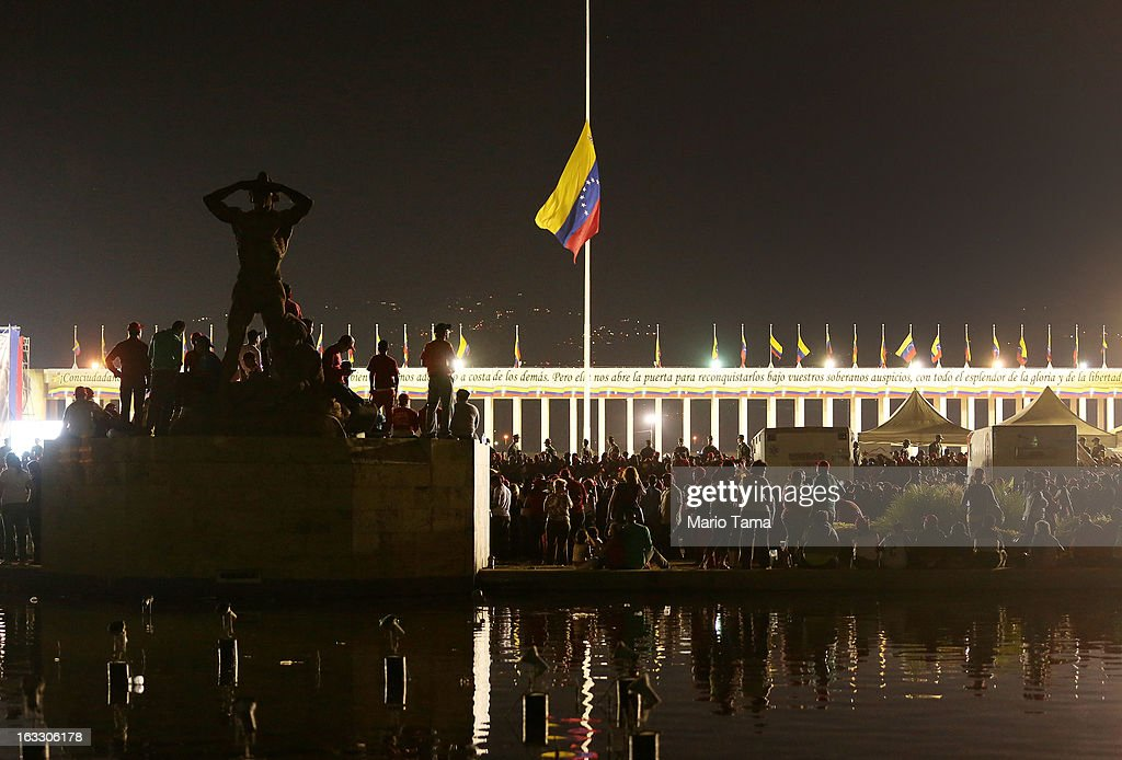 People gather and wait in line after dusk to view the remains of late Venezuelan President Hugo Chavez outside the Military Academy with the national flag at half-staff on March 7, 2013 in Caracas, Venezuela. Countless Venezuelans waited on a mile-long line to pay their last respects to Chavez before his funeral tomorrow.