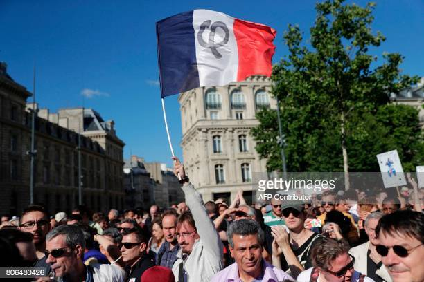 People gather and wave a French national flag as they listen to La France Insoumise leftist party's leader delivering a speech on Place de la...
