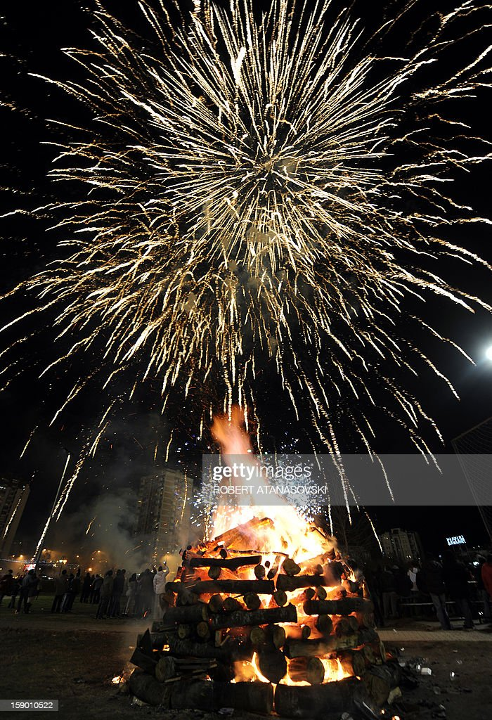 People gather around a bonfire and watch fireworks ahead of the Christian Orthodox Christmas, in Skopje on January 5, 2013. Christian Orthodox believers in Macedonia, who follow the Julian calendar, will celebrate Christmas on January 7.