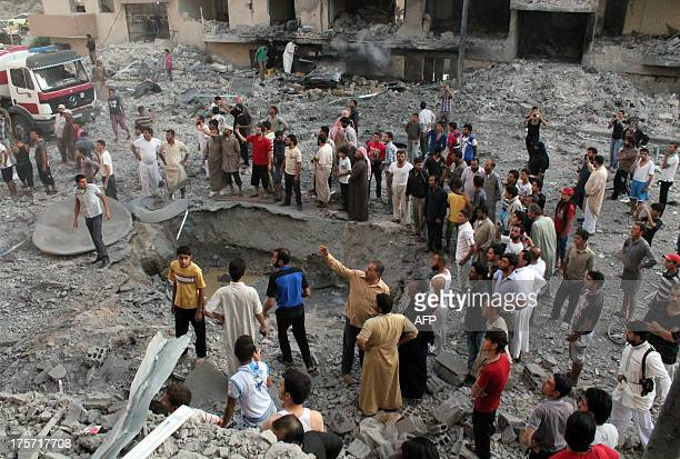 People gather around a crater at the scene of an explosion in the northern Syrian city of Raqqa early on August 7 2013 UN weapons inspectors tasked...