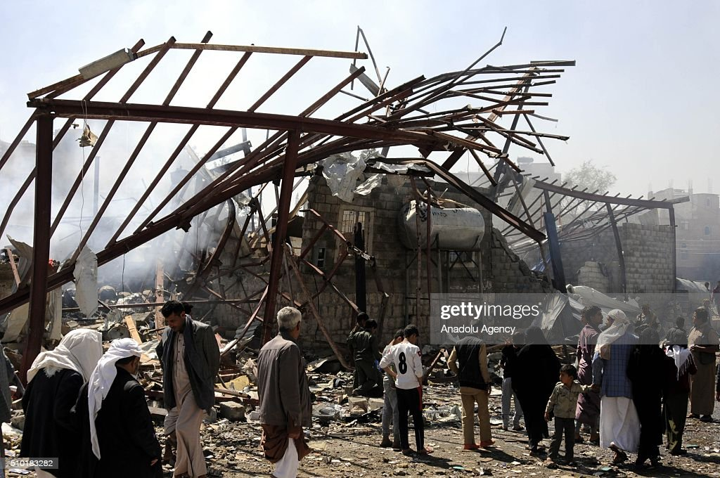 People gather around a destroyed building as Saudi-led coalition forces conduct airstrike to a building at Siraton neighborhood in Sana, capital city of Yemen, on February 14, 2016.