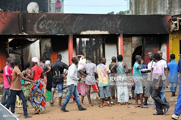 People gather around a destroyed commercial building on October 10 2015 in Conakry after at least two people were killed and a score hurt in clashes...
