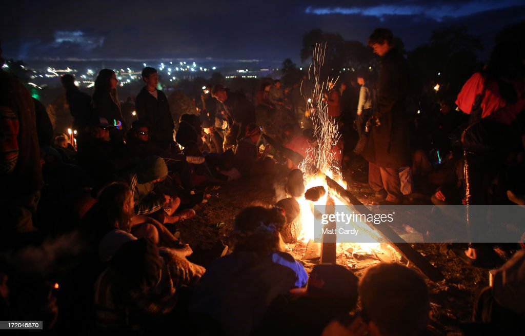 People gather around a fire at the Glastonbury Festival of Contemporary Performing Arts site at Worthy Farm, Pilton on July 1, 2013 near Glastonbury, England. Gates opened on Wednesday at the Somerset diary farm that plays host to one of the largest music festivals in the world and this year featured headline acts Artic Monkeys, Mumford and Sons and the Rolling Stones. Tickets to the event which is now in its 43rd year sold out in minutes and that was before any of the headline acts had been confirmed. The festival, which started in 1970 when several hundred hippies paid 1 GBP to watch Marc Bolan, now attracts more than 175,000 people over five days.