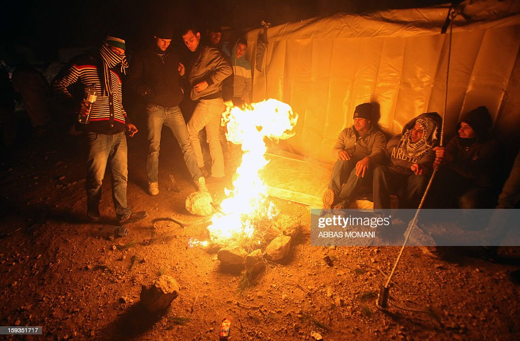 People gather around a fire near tents that Palestinian activists set up in an 'outpost' named Bab al-Shams ('Gate of the Sun') between Jerusalem and the Jewish settlement of Maale Adumim in the Israeli-occupied West Bank, in an area where Israel has vowed to build new settler homes, on January 12, 2013. Israeli authorities quickly issued expulsion orders, but activists' lawyers successfully petitioned the supreme court at night for a stay. After nightfall, the end of the Jewish sabbath, Prime Minister Benjamin Netanyahu's office said in a statement that he was seeking to have the injunction overturned. AFP PHOTO/ABBAS MOMANI