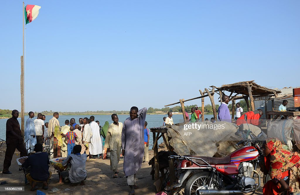 FORT -- People gather around a loading dock in Blangoua, on the lagoon which feeds into Lake Chad, on March 1, 2013. More and more security forces say it is probable that Nigerian Islamist extremist group Boko Haram, who claimed responsibility for the kidnapping of a French family on February 19 in northern Cameroon, have moved north towards Chad. 'What I want, its to catch the bastards' Marine captain and head of the Cameroonian Marine presence on Lake Chad Aboubakar said. Lake Chad, a huge area with small islands and canals separating it from Cameroon, Nigeria, Chad and Niger, is a possible hiding place for the kidnappers of the French family and their hostages. AFP PHOTO/PATRICK FORT
