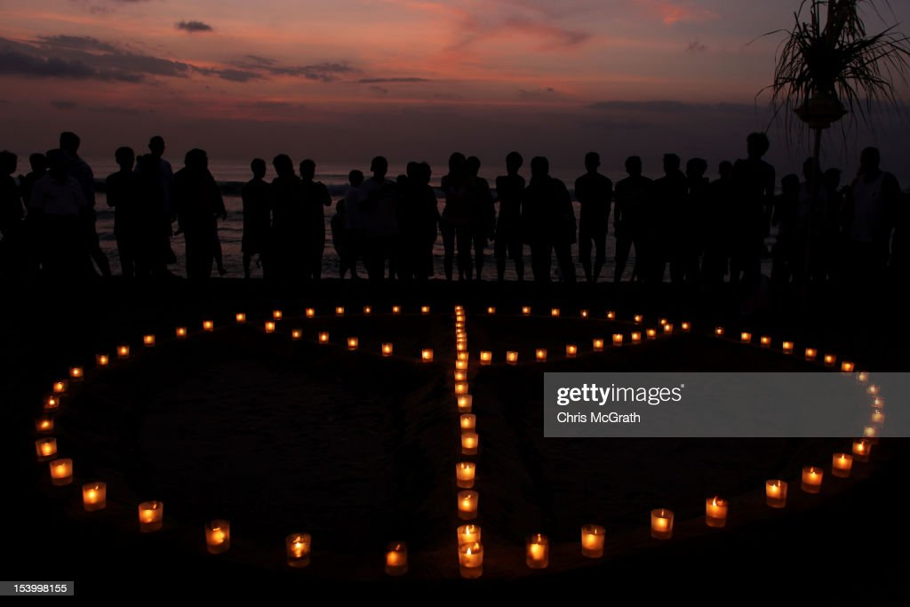 People gather around a peace sign made of candles as part of the Paddle for Peace memorial ceremony on Kuta Beach, Bali, on October 12, 2012 in Indonesia. Hundreds of foreign and local family members, friends and general public gathered at various memorial ceremonies through out the day to remember the victims of the 2002 Kuta nightclub bombings which killed 202 people, including 88 Australians.