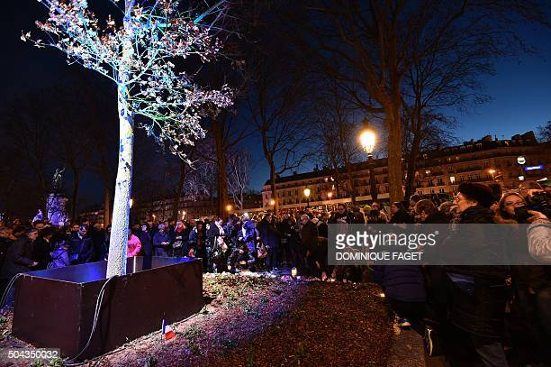 TOPSHOT People gather around a 'remembrance tree' an oak planted at the west end of the Place de la Republique square in honour of the attack victims...