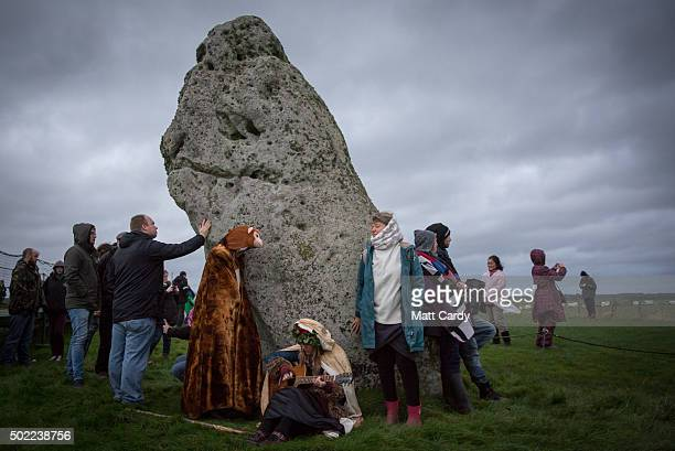 People gather around a stone as druids pagans and revellers gather at Stonehenge hoping to see the sun rise as they take part in a winter solstice...