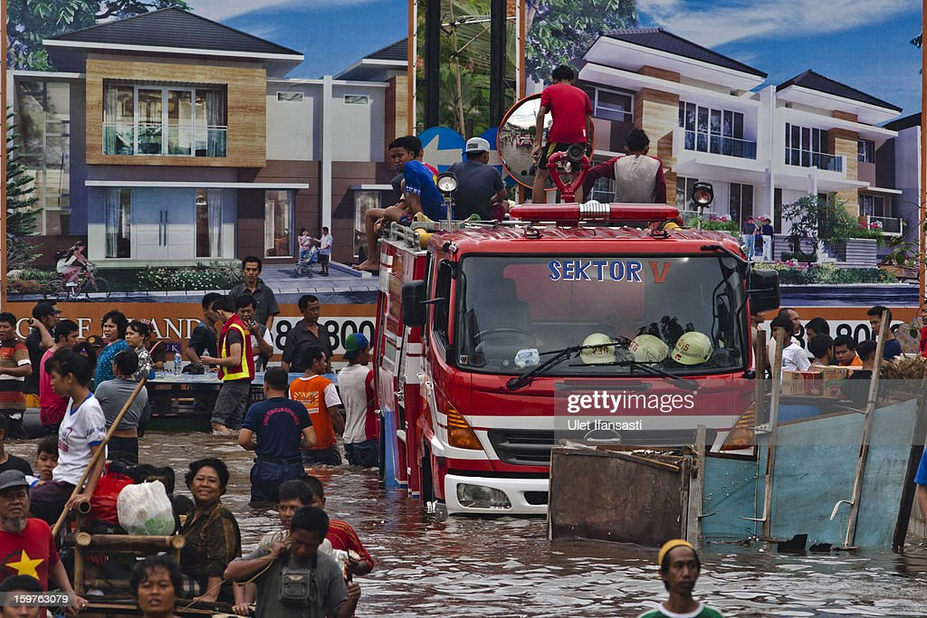 People gather around a stranded fire engine as major floods hit North Jakarta on January 20, 2013 in Jakarta, Indonesia. The death toll has risen to at least 21 since severe flooding struck the city on January 17. The US has offrered US$150,000 (Rp 1.44 billion) in aid.