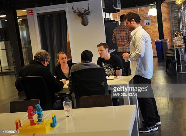 People gather around a table during a break at the 'WeWork' cooperative coworking space on March 13 2013 in Washington DCIn a large warehousetype...