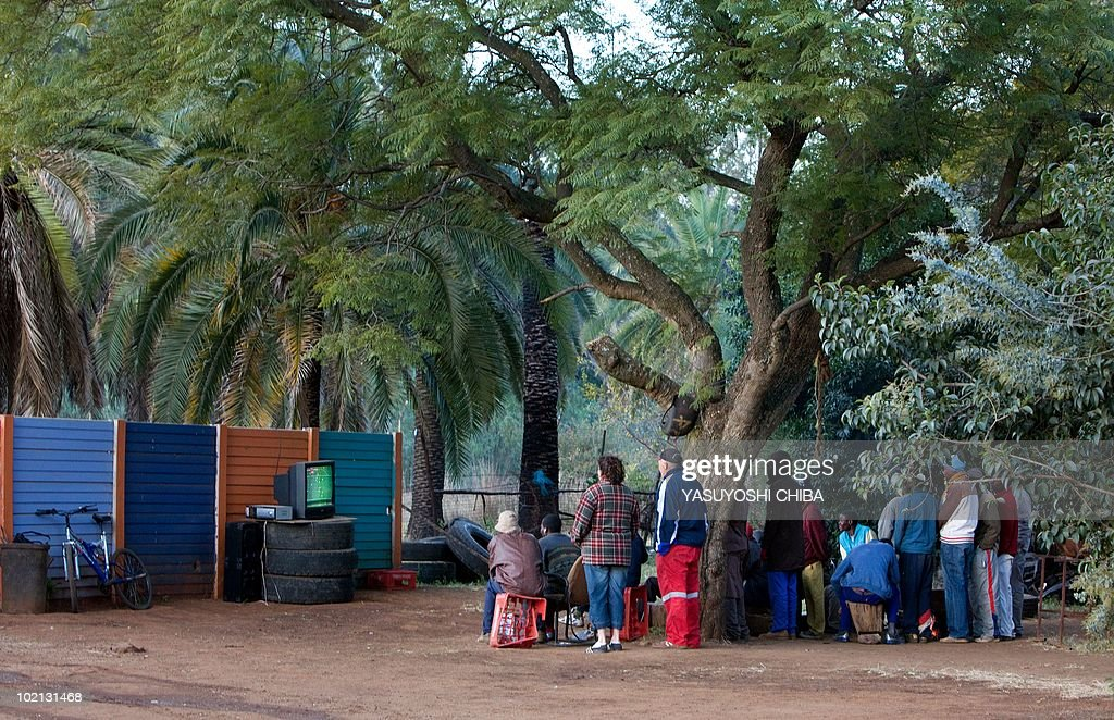 People gather around a television set up outside to watch the 2010 World Cup football match between Ivory Coast and Portugal near Pretoria on June 15, 2010. The public viewing was possible after a local Afrikaaner offered the television to the community where no electricity has been available for six years. AFP PHOTO / Yasuyoshi CHIBA