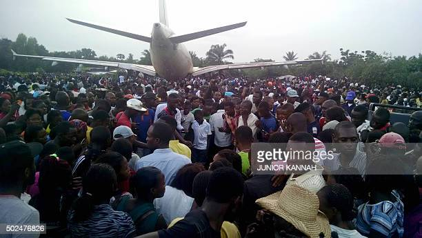 People gather around an Airbus A310 cargo jet that overshot the runway while landing in the central city of MbujiMayi on December 24 killing seven...
