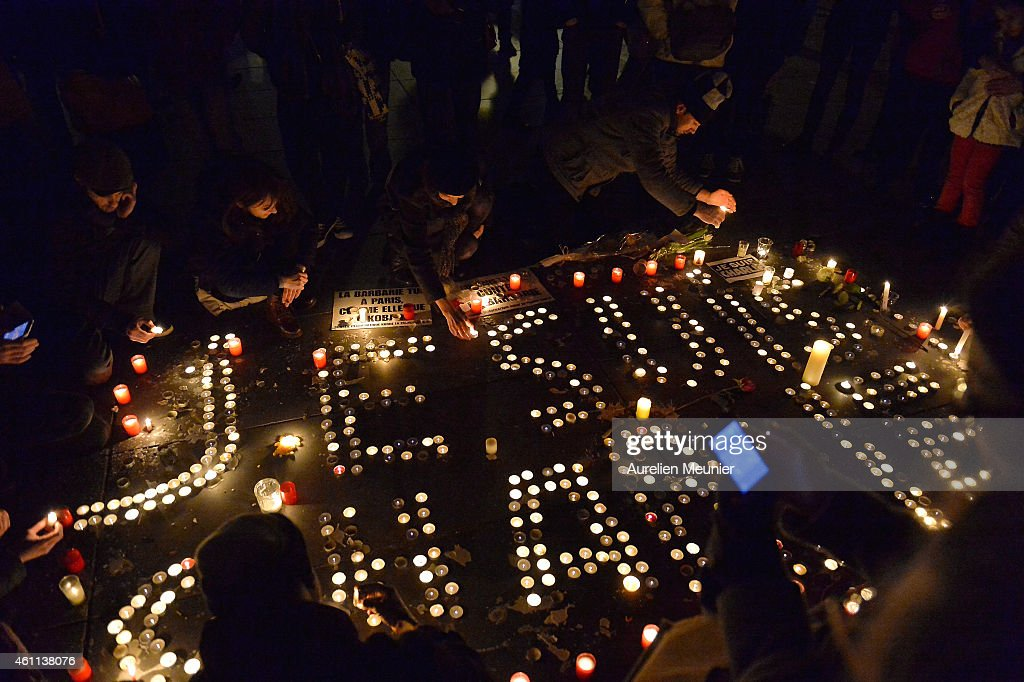 People gather around candles and pens at the Place de la Republique (Republic square) in support of the victims after the terrorist attack earlier today on January 7, 2015 in Paris, France. Twelve people were killed, including two police officers, as two gunmen opened fire at the offices of the French satirical publication Charlie Hebdo.